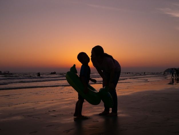 Silhouette mother kissing son on beach with orange evening sky background, family lifestyle.