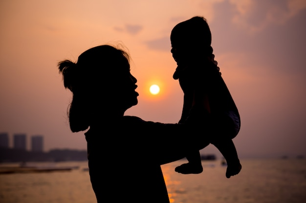 Silhouette of mother playing with her toddler at sunset