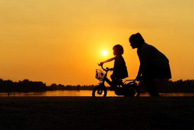 Silhouette of a mother who teaches daughter to ride a bike.