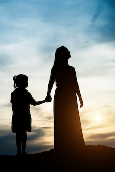 Silhouette of mother with her daughter standing and sunset