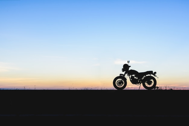 Silhouette of motorcycle with sunset background