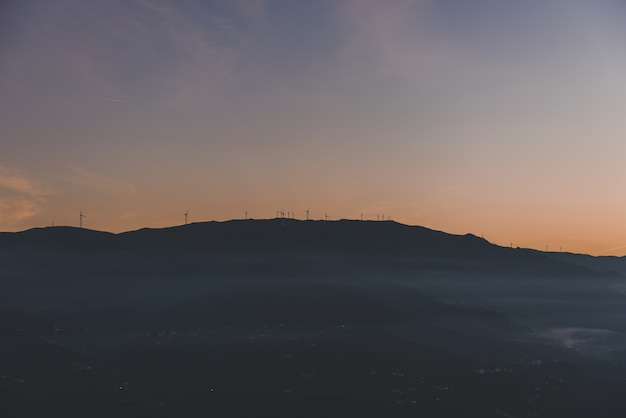 Silhouette of a mountain with windmills on the top