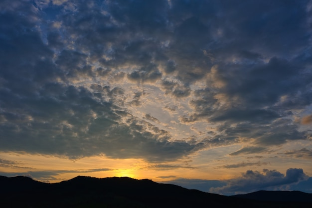 Silhouette of mountains against the background of the shining sun with beautiful clouds