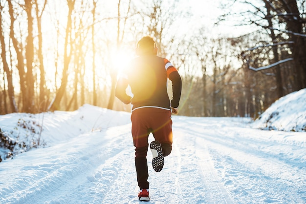 Silhouette of muscular young man hinking at sunrise in winter