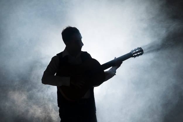 Silhouette of a musician on stage playing the guitar