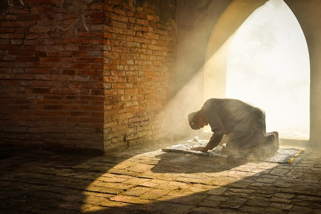 The silhouette of a muslim man praying in an old mosque in phra nakhon si ayutthaya province, asia muslim