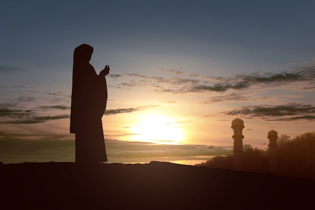 Silhouette of muslim woman in a veil standing while raised hands and praying
