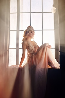 Silhouette of a mysterious fairy woman on the background of the window in the sunlight.