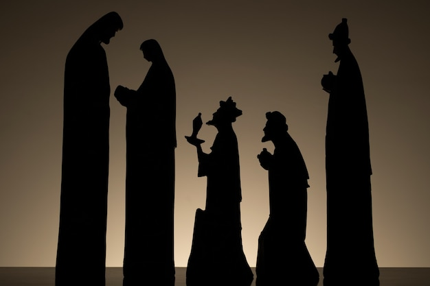 Silhouette of nativity scene with baby jesus on mary's lap, with joseph and the three wise men