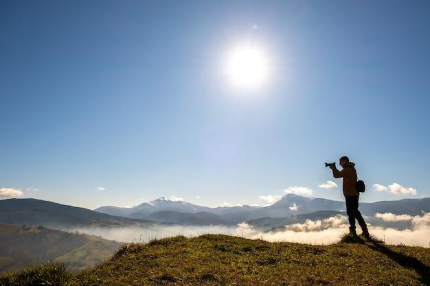 Силуэт фотографа туриста, снимающего утренний пейзаж в осенних горах с цифровой камерой.