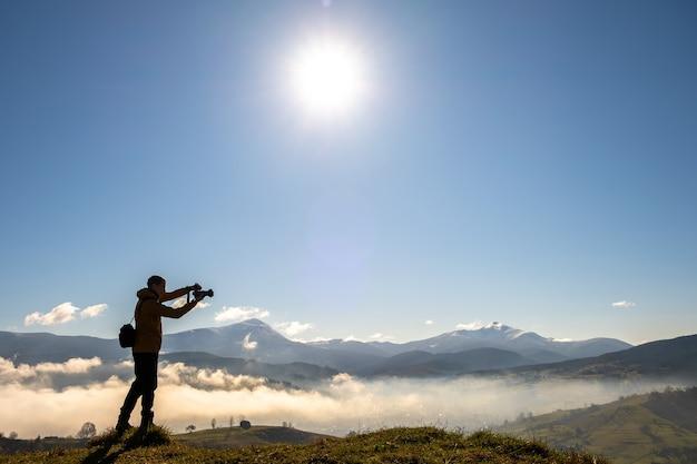 秋の山々の朝の風景の写真を撮るバックパッカー写真家のシルエット