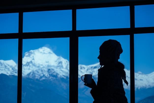 창문과 산 배경에 뜨거운 음료 한 잔을 들고 있는 아름다운 소녀의 실루엣