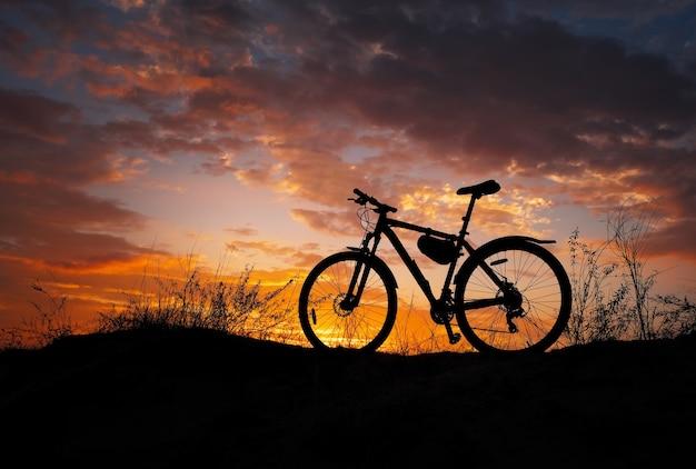 Силуэт велосипеда во время заката. песчаный луг. ни один. никто.