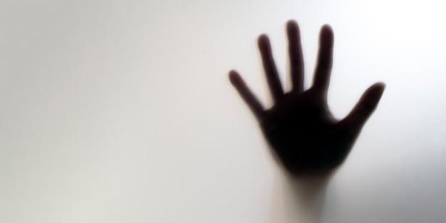 유리 뒤에 흐리게 손의 실루엣입니다. 도움과 가정 폭력을 요청하는 개념.