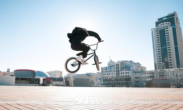 明るい夏の日に都市景観でジャンプするbmxライダーのシルエット