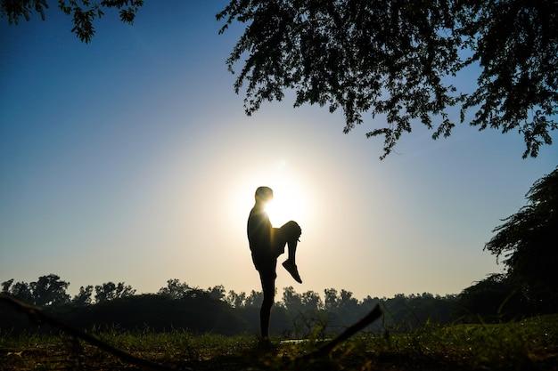 太陽と川の近くの公園でテコンドーキック練習をしている少年のシルエット