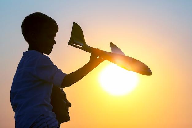 소년의 실루엣은 석양을 배경으로 하늘로 모형 비행기를 발사합니다. 미래 조종사의 어린 시절 꿈