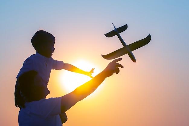 아버지의 어깨에 앉아 있는 소년의 실루엣은 석양을 배경으로 저녁 하늘로 모형 비행기를 발사합니다. 미래의 조종사를 꿈꾸는 아이들