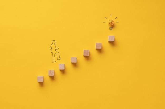 昇進と進歩の概念的なイメージで電球に向かって階段を上って歩いているビジネスマンのシルエット。