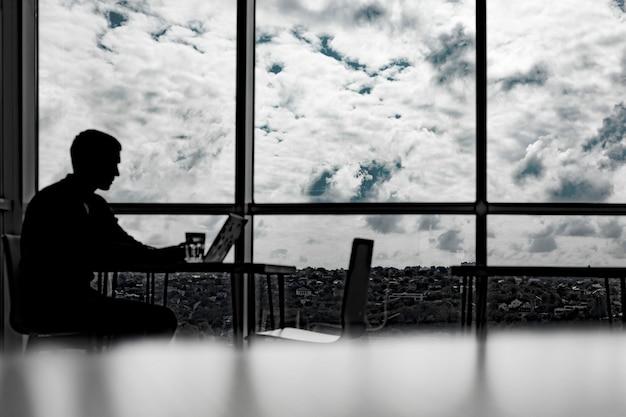 큰 창문이 있는 사무실에서 일하는 사업가의 실루엣.