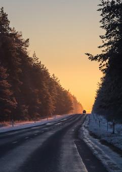 雪の降る冬の日没の光の中でアスファルト道路上の車のシルエット。