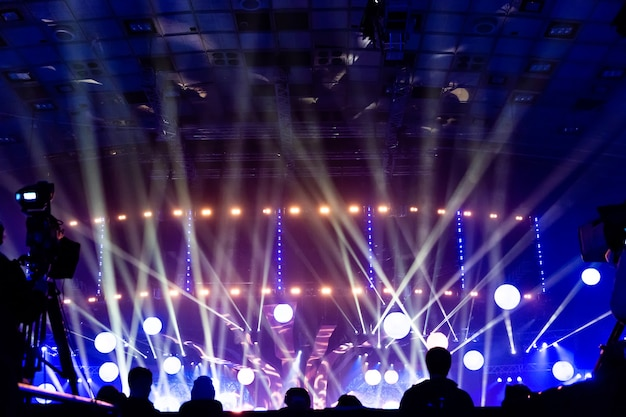 コンサートの群衆のシルエット。観客はステージに目を向けます。ロックコンサートでのパーティーの人々。ミュージカルパーティー。ミュージカルショー。グループシルエット。若い聴衆。