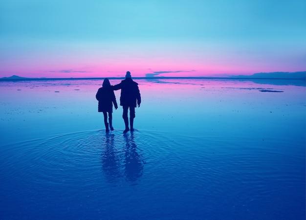 ボリビアの日没時にウユニ塩原の水面を歩くカップルのシルエット