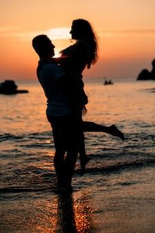 Силуэт влюбленная пара на закате на пляже - мужчина держит свою женщину на руках. романтические отношения. медовый месяц.
