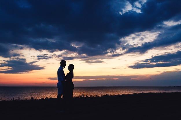 美しい夕日の空と海を愛するカップルのシルエット