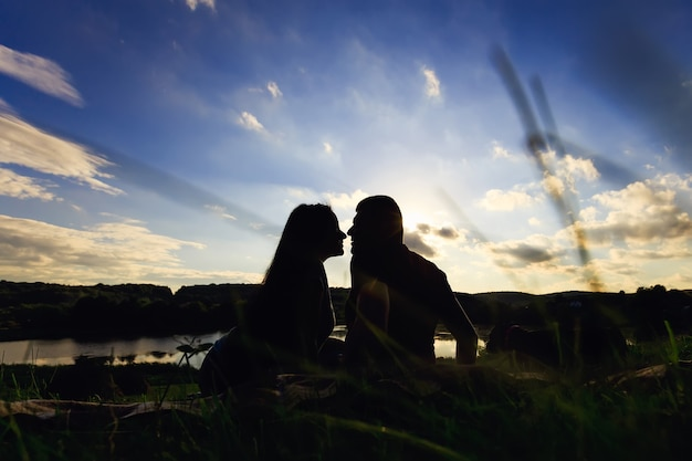 Силуэт пары, сидящей и целующейся на лугу на фоне красивого заката и природы
