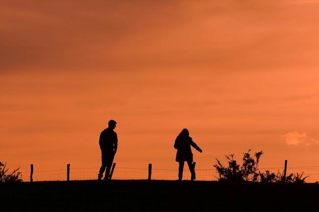 일몰과 함께 산에서 트레킹하는 커플의 실루엣