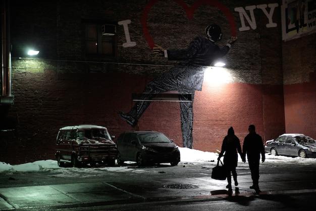 도시의 i love new york 기호 아래에서 밤에 걷는 커플의 실루엣