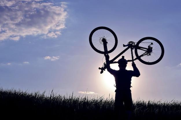 Силуэт велосипедиста с поднятым велосипедом в траве на солнце