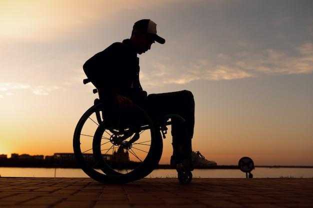 Силуэт инвалида в инвалидной коляске на фоне заката фото высокого качества