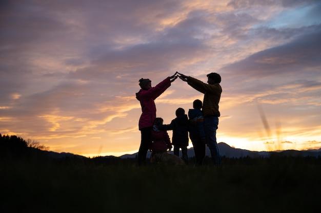 부모가 세 자녀와 개 위에 팔로 집을 만드는 아름다운 저녁 하늘 아래 외부 가족의 실루엣.