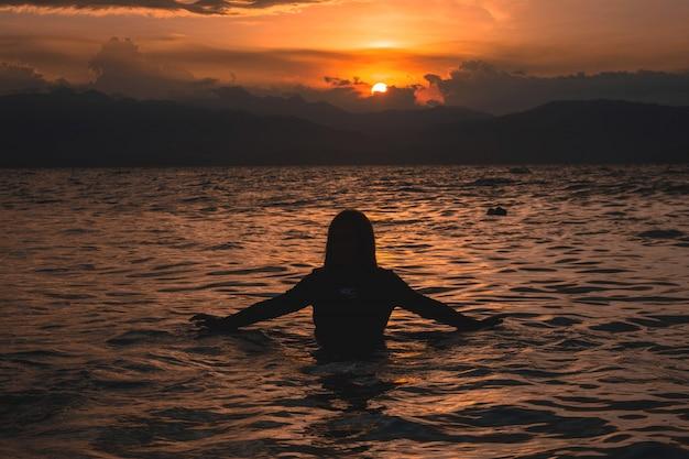 美しい日没時に海の水で半分の女性のシルエット