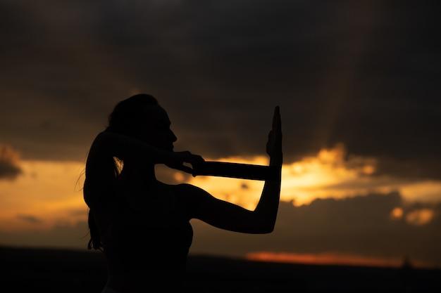 백그라운드에서 태양과 일몰에 스트레칭 피트 니스 여자의 실루엣.
