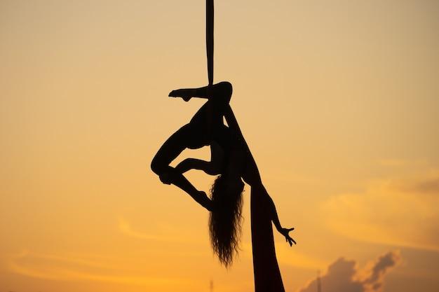 일몰 동안 공중 실크에 유연한 여자 곡예사의 실루엣. 개념 아름다움.
