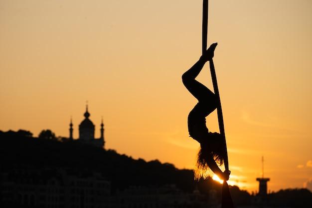 키예프 시내에서 일몰 동안 공중 실크에 유연한 여자 곡예사의 실루엣. 자유와 평화의 개념.