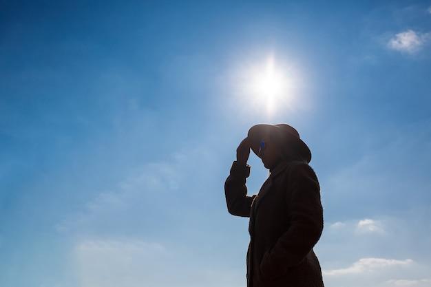 雲と太陽と空の背景に帽子とコートを着た女の子のシルエット。
