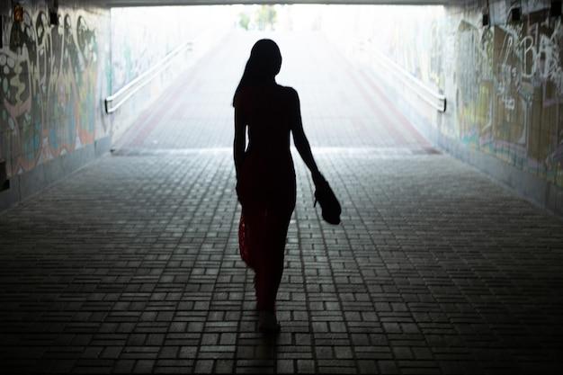 地下横断歩道の出口に行く長いドレスを着た女の子のシルエット。ソフトフォーカス。概要。