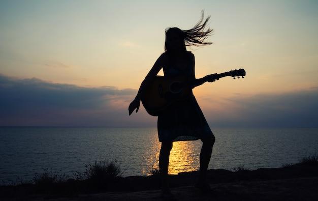 Силуэт девушки в сарафане, играющей на гитаре на фоне морского заката