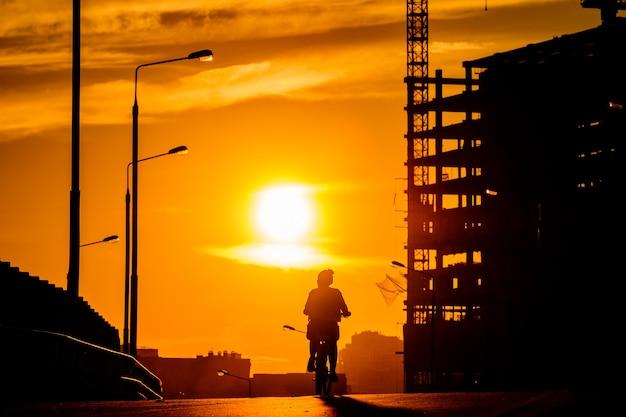 日没時の橋の上の自転車に乗っている女の子のシルエット。