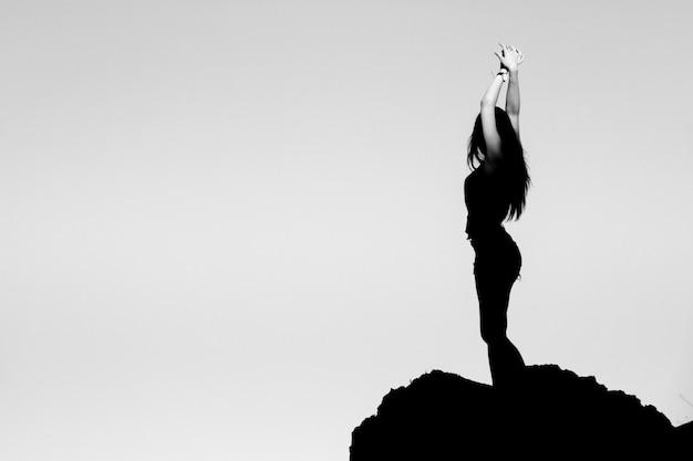 Силуэт девушки на вершине горы.