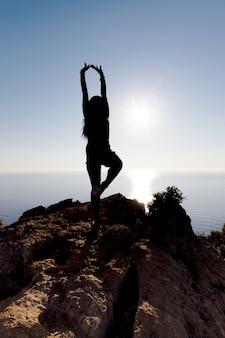 海と夕日の丘、自由の状態でヨガに従事している女の子のシルエット