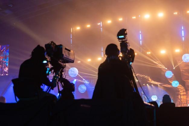 이벤트를 방송하는 카메라맨 그룹의 실루엣. 작업자는 높은 플랫폼에 있습니다.