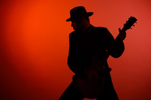 Силуэт гитариста в шляпе на красном