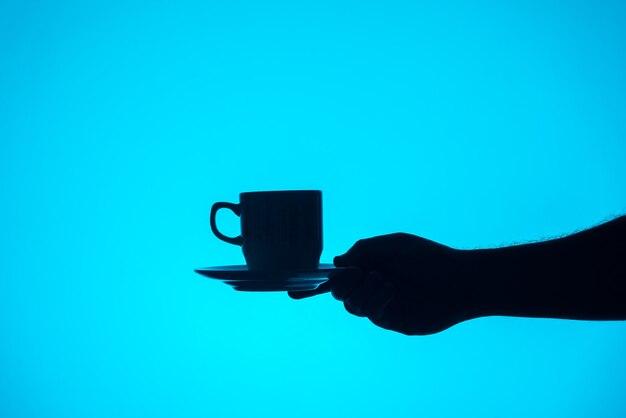 青い背景にコーヒーを持っている手のシルエット