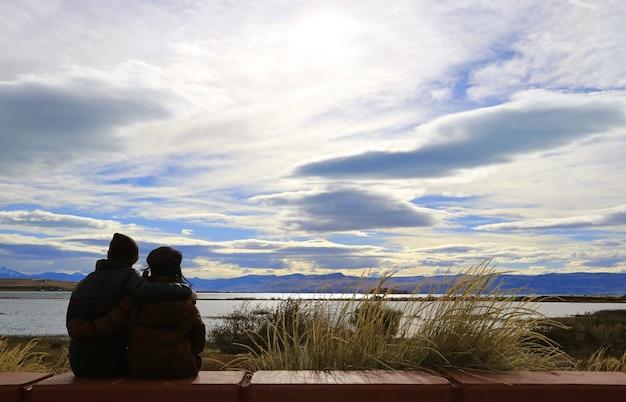 アルゼンチン、パタゴニア、エルカラファテのアルゼンチン湖岸でリラックスした幸せなカップルのシルエット