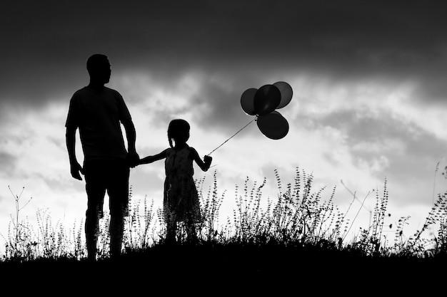 風船と子供を持つ幸せな家族の父のシルエット